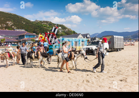A small collection of childrens amusements on a sandy beach, in the foreground the donkey riders are just beginning - Stock Photo