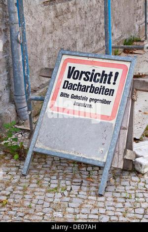 Sign on scaffolding, Vorsicht! Dacharbeiten, Bitte Gehsteig gegenueber benutzen, German for Caution! Roofing work - Stock Photo