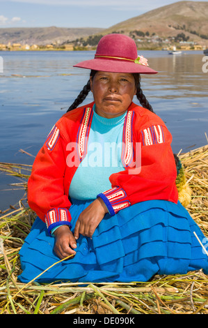 Uru woman in traditional dress on one of the floating reed islands of the Uros people, Lake Titicaca, near Puno, - Stock Photo
