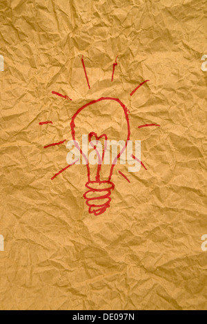 Idea light bulb drawing on crumpled yellow paper texture. - Stock Photo