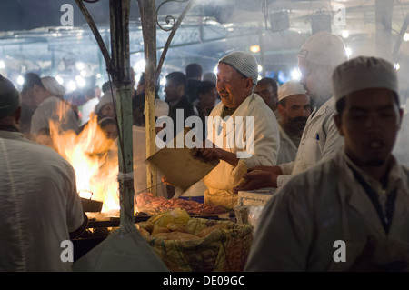 Cook fanning flames ready to cook sausages, at a foodstall in the Djemaa el-Fna square, Marrakech, Morocco - Stock Photo
