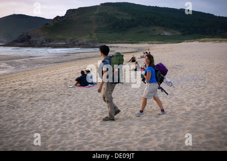 Many pilgrims come to one of the beaches in Finisterre to see the sunset after finishing the whole tour of the Way - Stock Photo