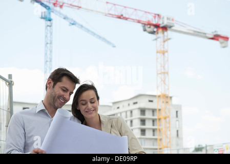 Architects reviewing blueprint in construction site - Stock Photo