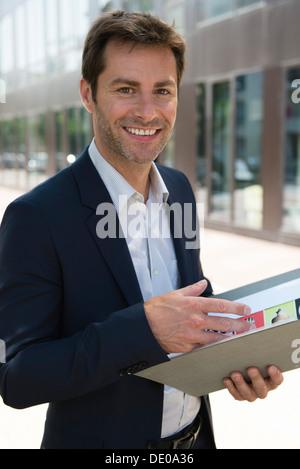 Businessman holding folder, portrait - Stock Photo