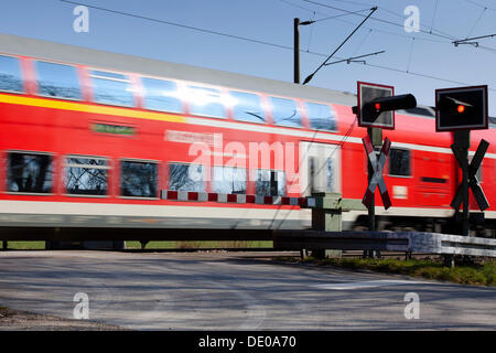 Railway crossing with passing train - Stock Photo