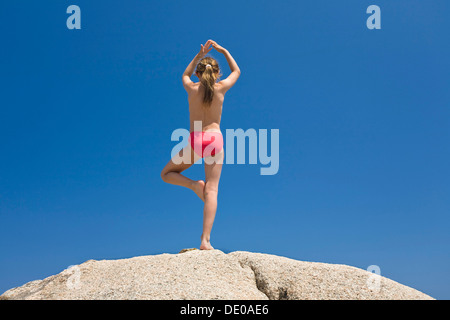 7-year-old girl doing Yoga on the rocks of Palombaggia beach, south-east coast, Balagne region, Corsica, France, - Stock Photo