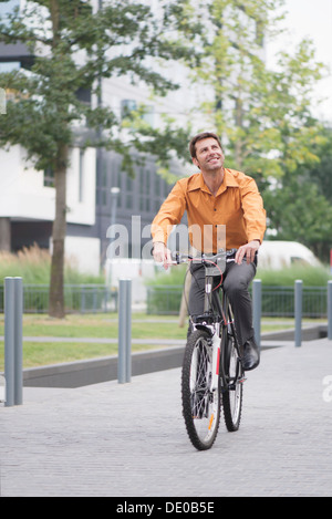 Man in business attire riding bicycle - Stock Photo