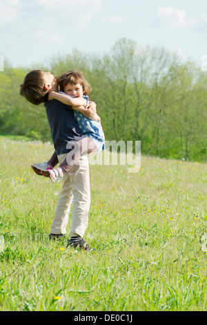 Young siblings embracing outdoors - Stock Photo
