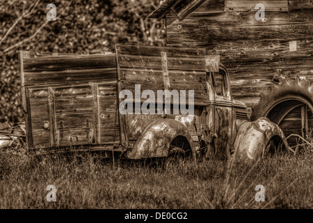 Rural setting of old rustic, antique, farm truck, sitting in front of an old barn or shed, Tractor tire in background. - Stock Photo