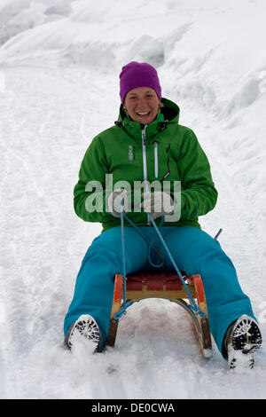 Sled driver driving down into the valley, Zillertal, Austria - Stock Photo