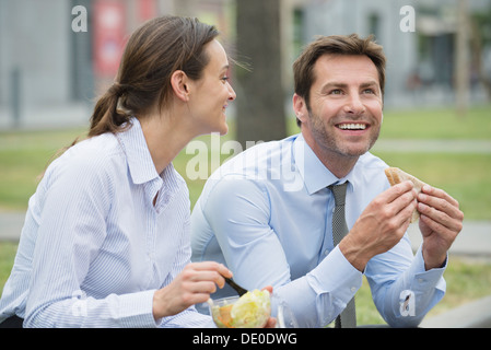 Coworkers having lunch together outdoors - Stock Photo