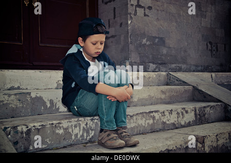 a lonely and sad boy sitting on the dirty stairs - Stock Photo