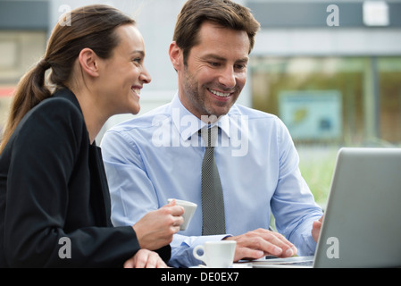 Business associates having coffee while collaborating on project - Stock Photo