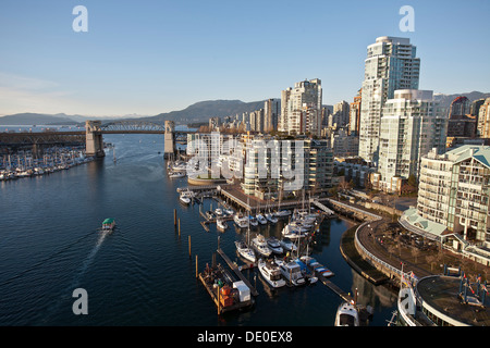 Yaletown neighborhood and the false creek viewed from the Granville Bridge. English Bay and the Burrard Britge at - Stock Photo