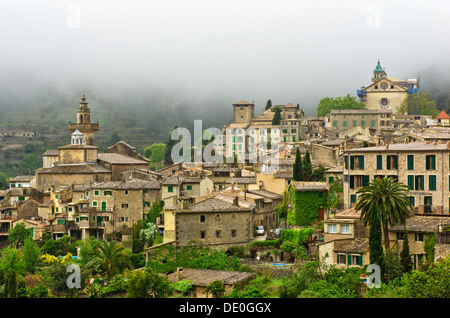 Village view with rain clouds, behind the Carthusian monastery, in front the parish church of Sant Bartomeu, Valldemossa, - Stock Photo