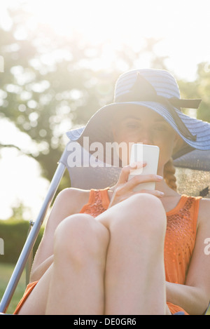 Young woman relaxing outdoors with smartphone - Stock Photo