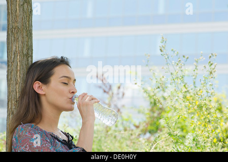 Woman drinking bottled water outdoors - Stock Photo