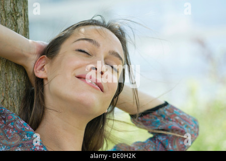 Woman relaxing outdoors, portrait - Stock Photo