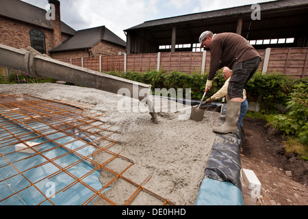 self building house, pouring readymixed concrete steel mesh reinforced prepared floor slab, two men raking level - Stock Photo