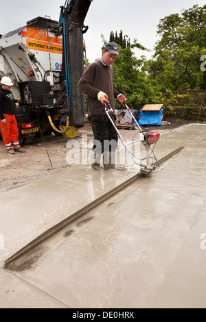 self building house, man using single beam vibrating screed to tamp down readymixed concrete floor slab level - Stock Photo