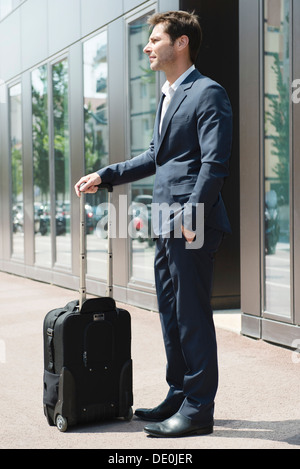 Businessman standing and waiting with luggage - Stock Photo