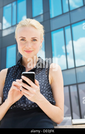 Young businesswoman using smartphone outdoors - Stock Photo