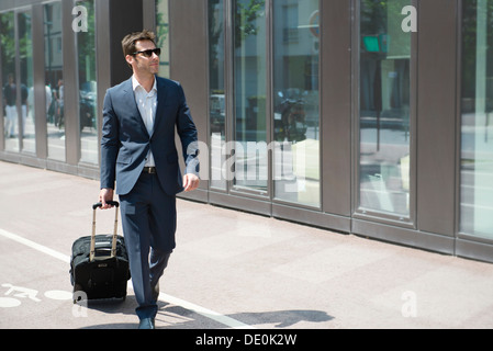 Businessman with sunglasses pulling luggage, walking in city - Stock Photo