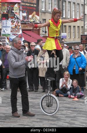 Chinese Woman Unicyclist Balaning On a Unicycle, The Royal Mile, Edinburgh, Scotland, UK - Stock Photo