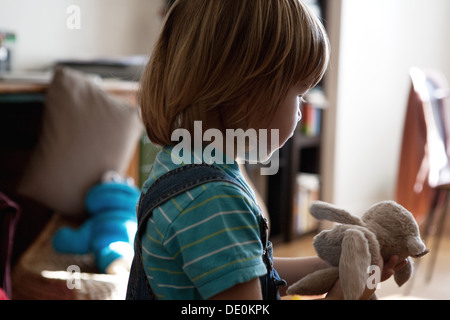 Little boy playing with stuffed toy - Stock Photo