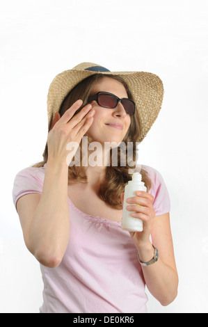 Young woman with sunglasses and a straw hat - Stock Photo