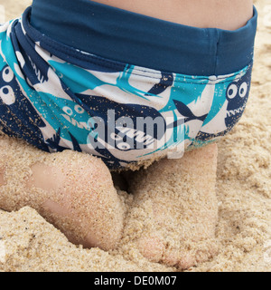 Boy sitting on sand at the beach, close-up - Stock Photo