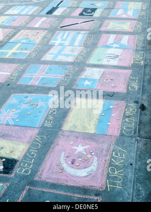 Pavement art in Trafalgar Square, London, UK - colourful chalk drawings of national flags of the world - Stock Photo