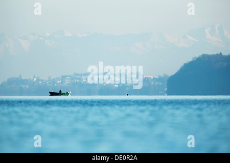 Fishing boat on Lake Constance with the Alps at back - Stock Photo
