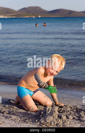Boy, 5 years, on a sandy beach, digging in the sand - Stock Photo