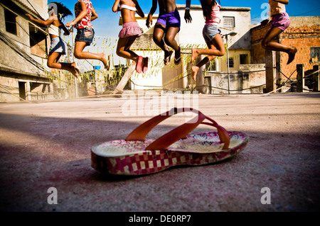 Child's play at Favela do Jacarezinho in Rio de Janeiro, Brazil. 10-14 years-old happy girls jump rope - Stock Photo