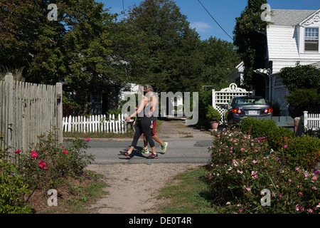 An athletic couple strolls down the  East End of Commercial Street in Provincetown Massachusetts on a summer Sunday - Stock Photo