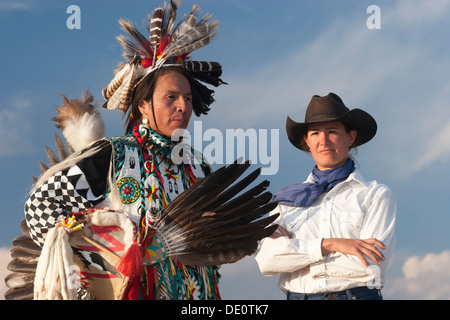 Cowgirl with native American man wearing traditional Cheyenne outfit - Stock Photo