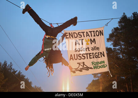 Protest against a nuclear waste transport, an activist of the environmental organization Robin Wood hanging above - Stock Photo