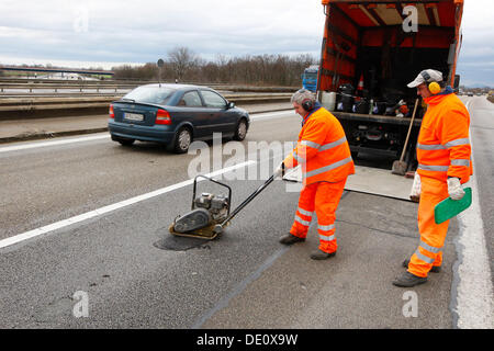Workers doing road rehabilitation after frost on the A5 motorway near Heidelberg, Baden-Wuerttemberg - Stock Photo