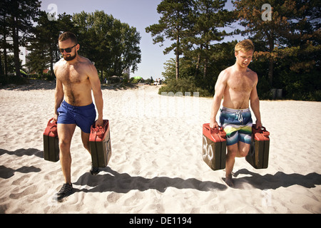Two tough young male crossfitters lifting heavy jerrycans and walking during a crossfit workout on the beach. - Stock Photo