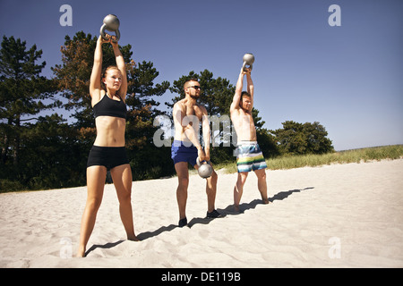 Group of athletes swinging a kettle bell over their head on beach. Young people doing crossfit workout on a hot - Stock Photo