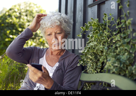 Elder woman sitting on a bench in her backyard reading text message on her mobile phone - Stock Photo