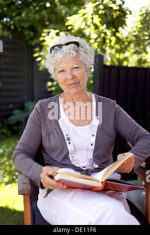 Happy mature woman sitting on a chair in garden with a book looking at camera smiling - Elder woman reading outdoors - Stock Photo