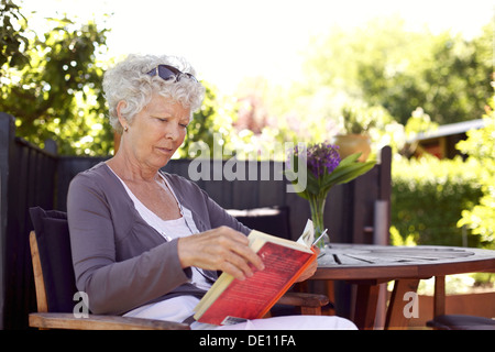 Relaxed senior woman sitting a chair in backyard garden reading a book - Stock Photo