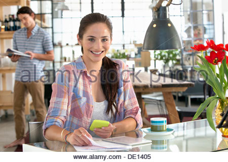 Portrait of smiling woman with cell phone and paperwork at kitchen table - Stock Photo