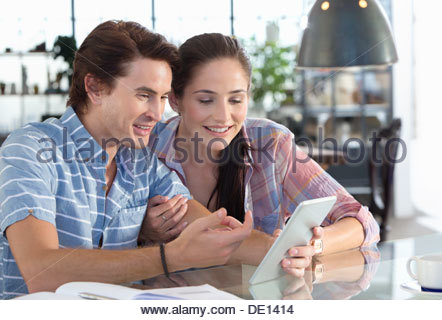 Smiling couple using digital tablet at kitchen table - Stock Photo