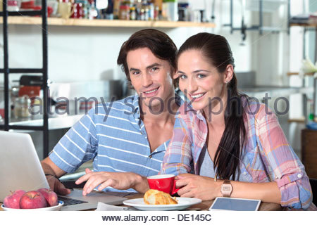 Portrait of smiling couple using laptop at kitchen table - Stock Photo