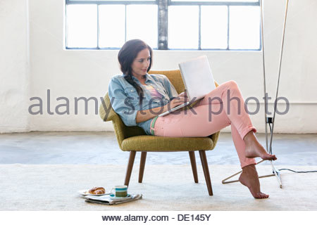 Woman using laptop in armchair - Stock Photo