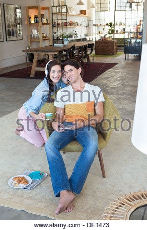 Portrait of smiling couple listening to music on headphones with digital tablet in livingroom - Stock Photo