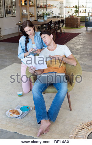 Couple with paperwork and laptop in livingroom - Stock Photo